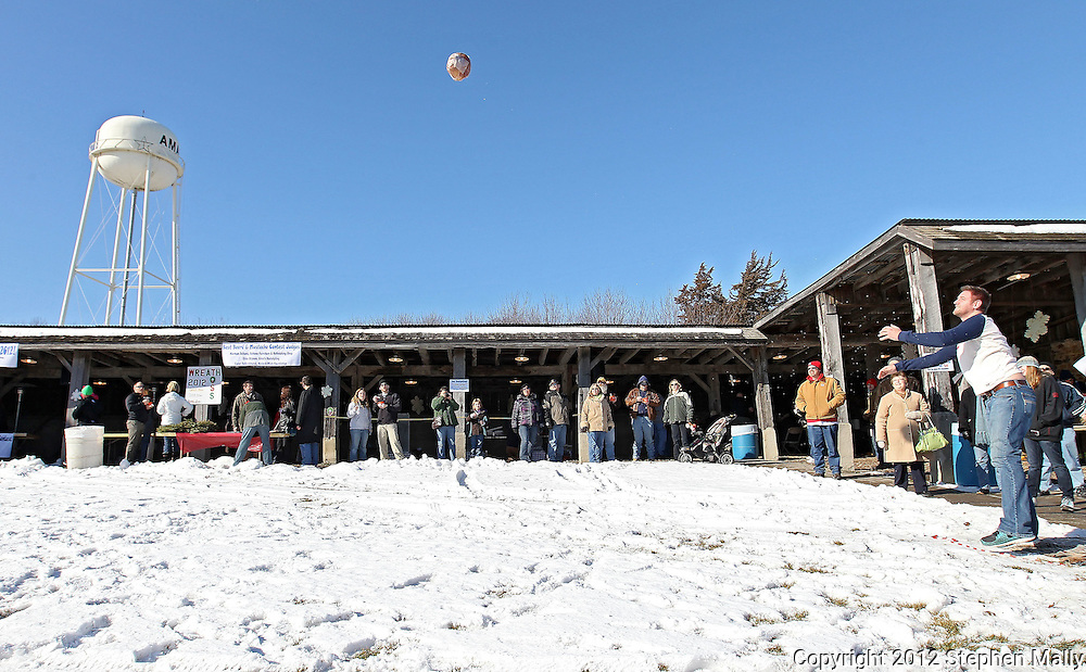 "Sean Giese (right) of Tulsa, Oklahoma, watches his 13-pound ham go flying through the air as he competes in the Great Amana Ham-Put during Winterfest at the Market Barn in Amana on Saturday, January 28, 2012. Giese, who is in Iowa visiting friends, threw his ham 34'10"". (Stephen Mally/Freelance)"