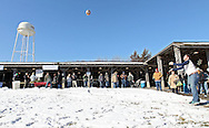 """Sean Giese (right) of Tulsa, Oklahoma, watches his 13-pound ham go flying through the air as he competes in the Great Amana Ham-Put during Winterfest at the Market Barn in Amana on Saturday, January 28, 2012. Giese, who is in Iowa visiting friends, threw his ham 34'10"""". (Stephen Mally/Freelance)"""