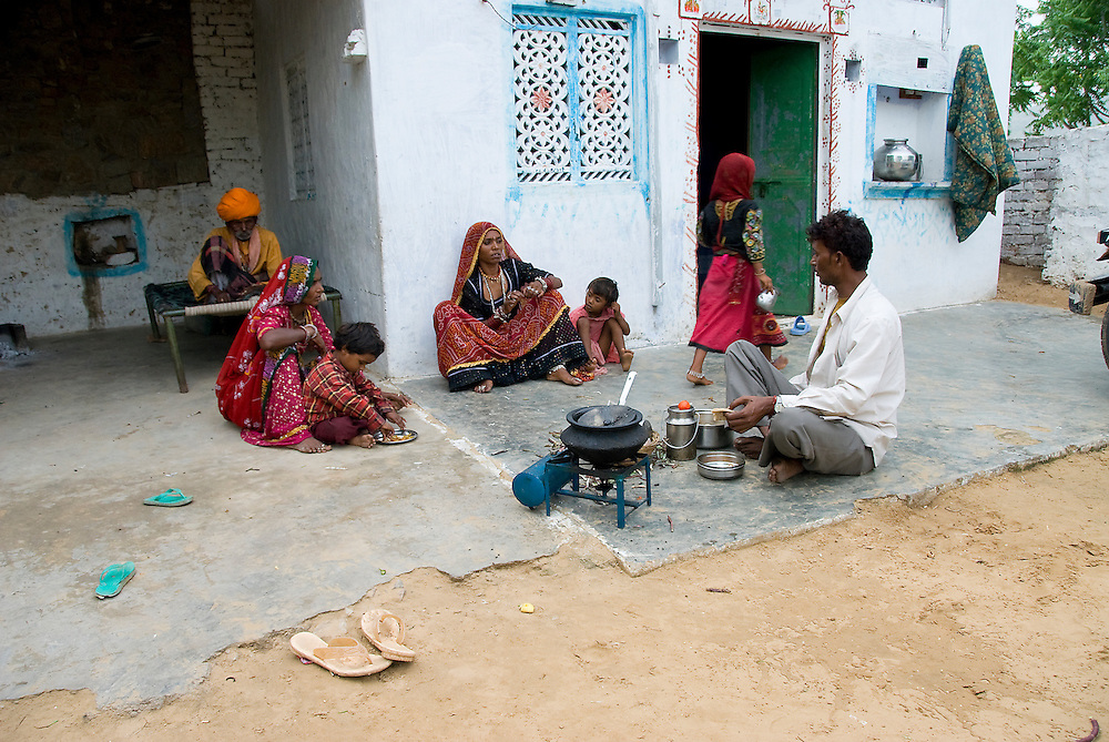 A father prepares chapati (unleavened bread) for his family and in-laws in front of his house in a Rajasthani village in the Thar desert (India)