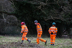 Denham, UK. 4 February, 2020. Engineers and a security guard walk across land cleared for works for the HS2 high-speed rail link project in front of an ancient alder tree with a girth of 11.6m and the river Colne. Planned works in the immediate vicinity are believed to include the felling of 200 trees and the construction of a roadway, Bailey bridge, compounds, fencing and a parking area. There is a wetland nature reserve forming part of a Site of Metropolitan Importance for Nature Conservation (SMI) on the other side of the river. Credit: Mark Kerrison/Alamy Live News