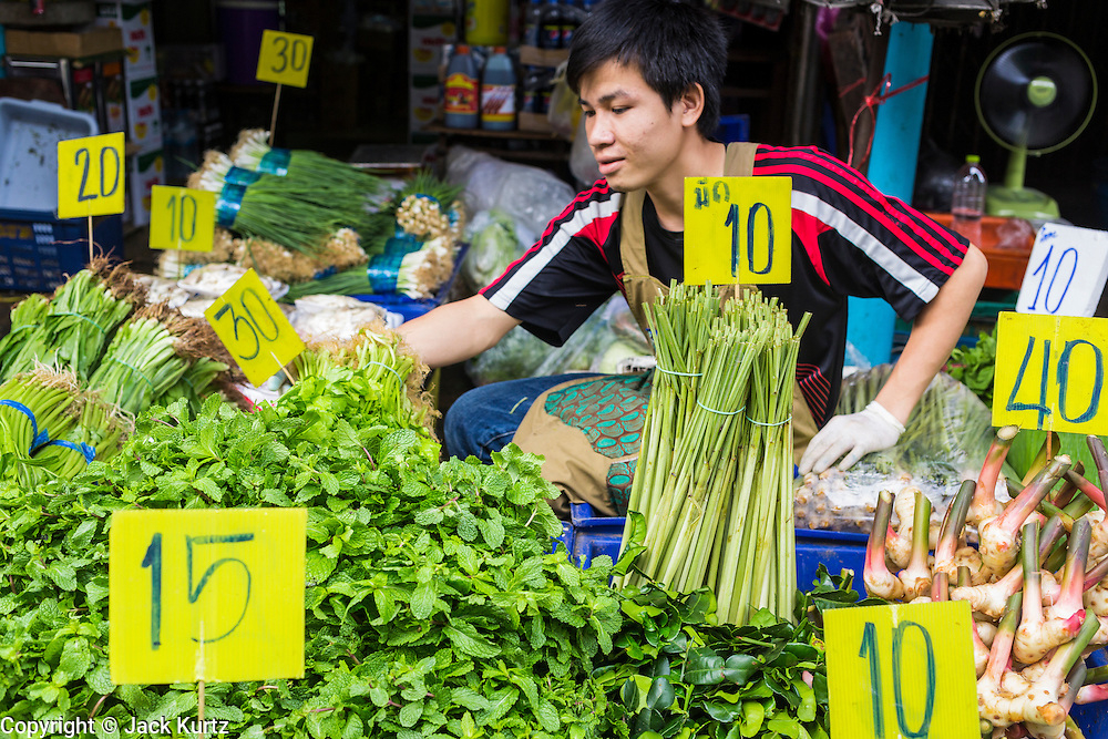 """24 AUGUST 2013 - BANGKOK, THAILAND: A produce vendor sits among the produce he was selling and their price signs in Khlong Toei Market in Bangkok. Thailand entered a """"technical"""" recession this month after the economy shrank by 0.3% in the second quarter of the year. The 0.3% contraction in gross domestic product between April and June followed a previous fall of 1.7% during the first quarter of 2013. The contraction is being blamed on a drop in demand for exports, a drop in domestic demand and a loss of consumer confidence. At the same time, the value of the Thai Baht against the US Dollar has dropped significantly, from a high of about 28Baht to $1 in April to 32THB to 1USD in August.     PHOTO BY JACK KURTZ"""