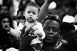 London, August 29th 2016. A toddler is held aloft above the crushing crowd on Ladbroke Grove during day two of Europe's biggest street party, the Notting Hill Carnival.