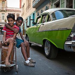 Boys having fun with an old suitcase close to a vintage car. Ciudad de La Habana, Cuba, Caribbean.