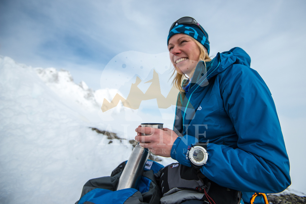 Squash Falconer, a female British adventurer, as seen holding a mug of warm tea on a snowy ridge of Aiguilles Marbrées on a cold and cloudy Winter afternoon in Mont Blanc Massif.