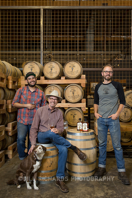 Tucson, AZ -- 09/28/2017<br /> <br /> (L- R) Hamilton Distillers' assistant distiller Ram&oacute;n Olivas and his dog Scarlet, founder Stephen Paul and head distiller and maltser Nathan Thompson Avelino photographed in the barrel room at the Tucson distillery. <br /> <br /> Hamilton Distillers, makers of Whiskey Del Bac, is the first craft distillery in Southern Arizona since prohibition. The company produces three distinct single malt whiskeys, including Whiskey Del Bac Dorado which is malted over mesquite.<br /> <br /> The distillery offers tours and tastings on Saturdays at 3 p.m <br /> <br /> Photography by Jill Richards