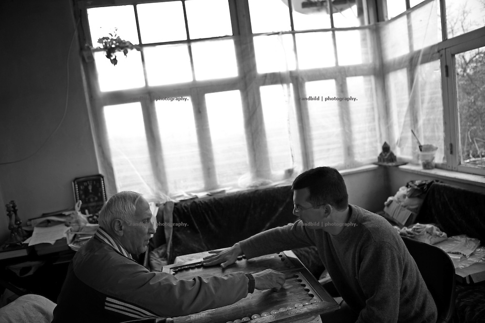 "Albert Khatchatrian and Armen Rakedjan play backgammon. This image is part of the photoproject ""The Twentieth Spring"", a portrait of caucasian town Shushi 20 years after its so called ""Liberation"" by armenian fighters. In its more than two centuries old history Shushi was ruled by different powers like armeniens, persians, russian or aseris. In 1991 a fierce battle for Karabakhs independence from Azerbaijan began. During the breakdown of Sowjet Union armenians didn´t want to stay within the Republic of Azerbaijan anymore. 1992 armenians manage to takeover ""ancient armenian Shushi"" and pushed out remained aseris forces which had operate a rocket base there. Since then Shushi became an ""armenian town"" again. Today, 20 yeras after statement of Karabakhs independence Shushi tries to find it´s opportunities for it´s future. The less populated town is still affected by devastation and ruins by it´s violent history. Life is mostly a daily struggle for the inhabitants to get expenses covered, caused by a lack of jobs and almost no perspective for a sustainable economic development. Shushi depends on donations by diaspora armenians. On the other hand those donations have made it possible to rebuild a cultural centre, recover new asphalt roads and other infrastructure. 20 years after Shushis fall into armenian hands Babies get born and people won´t never be under aseris rule again. The bloody early 1990´s civil war has moved into the trenches of the frontline 20 kilometer away from Shushi where it stuck since 1994. The karabakh conflict is still not solved and could turn to an open war every day. Nonetheless life goes on on the south caucasian rocky tip above mountainious region of Karabakh where Shushi enthrones ever since centuries."