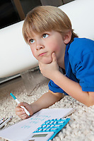 Boy contemplating while doing homework in house