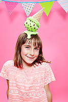 Tween brown haired girl wearing mint chocolate chip ice cream cone hat against pink seamless.<br /> Photographed at the Photoville Photo Booth September 20, 2015