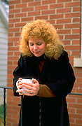 Woman age 27 holding morning coffee in the cool autumn.  Western Springs  Illinois USA