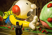 New York, NY – 27 November 2019. Thousands of spectators packed the streets around the American Museum of Natural History to see the inflation area for the balloons for Macy's Thanksgiving Day Parade. A man takes a photograph as the Wimpy Kid looks on.