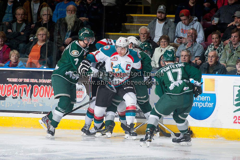 KELOWNA, CANADA - JANUARY 24: Madison Bowey #4 of Kelowna Rockets gets tangled up while digging for the puck at the boards against the Everett Silvertips on January 24, 2015 at Prospera Place in Kelowna, British Columbia, Canada.  (Photo by Marissa Baecker/Shoot the Breeze)  *** Local Caption *** Madison Bowey;