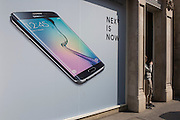 Phone user walks past Samsung shop window ad for new S6 model.
