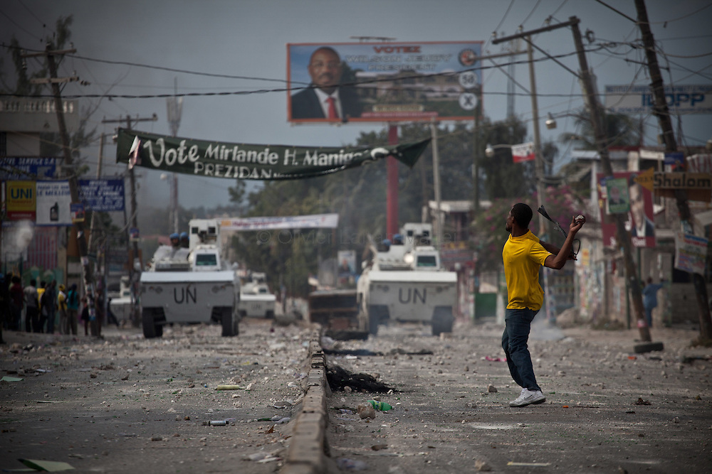Martelly's supporters demonstrate, in the streets of Port-au-Prince, to protest against the results of the presidential elections and the defeat of their leader, Michel Martelly. /// A Martelly's supporter throws a stone against Minstah's tanks, in a street of Port-au-Prince.