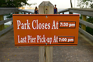 South Merrick, New York, U.S. 14th July 2013. At 7:07 PM, visitors at the Levy Park and Preserve fishing pier are approaching from behind an information sign, as National Weather Service extends its Heat Advisory in Long Island, New York, through to next day. South Shore winds helped those at park cope with the dangerous heatwave spreading throughout the Northeast, 92 degrees Fahrenheit, 33 degrees Celsius. The park close less than half an hour later, at 7:30 PM.