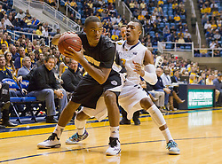 Wofford terriers guard Derrick Brooks (1) is trapped in a corner by West Virginia Mountaineers guard Jevon Carter (2) during the first half at the WVU Coliseum.