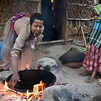 Wubalem prepares a breakfast of injera (a yeast-risen flat bread) with her daugher Rekebki in the kitchen area at the back of their home.<br /> <br /> Wubalem Shiferaw, age 23, lives in the village of Mecha with her husband Tsega Bekele, age 33, and their daughter Rekebki, age 4. Wubalem remembers her grandparents harvesting honey. She has maintained this tradition while moving to modern hives which produce a far greater yield of honey. Wubalem is a member of the Mecha village Cooperative which brings together local women beekeepers allowing them to share insights and build a credit union. The Mecha village Cooperative is not yet a member of the Zembaba Union. Wubalem's husband Tsega is a priest and a tailor. <br /> <br /> Harvesting honey supplements the income of small farmers in the Ethiopian region of Amhara where there is a long tradition of honey production. However, without the resources to properly invest in production and the continued use of of traditional, low-yielding hives, farmers have not been able to reap proper reward for their labour. <br /> <br /> The formation of the Zembaba Bee Products Development and Marketing Cooperative Union is an attempt to realize the potential of honey production in Amhara and ensure that the benefits reach small producers. <br /> <br /> By providing modern, high-yield hives, protective equipment and training to beekeepers, the Cooperative Union helps increase production and secure a steady supply of honey for which there is growing demand both in and beyond Ethiopia. The collective processing, marketing and distribution of Zembaba's &quot;Amar&quot; honey means that profits stay within the cooperative network of 3,500 beekeepers rather than being passed onto brokers and agents. The Union has signed an agreement with the multinational Ambrosia group to supply honey to the export market. <br /> <br /> Zembaba Bee Products Development and Marketing Cooperative Union also provides credit to individual members and trains carpenters in the production of modern hives. <br /> <br /> Photo: Tom Pietrasik<br /> Mech