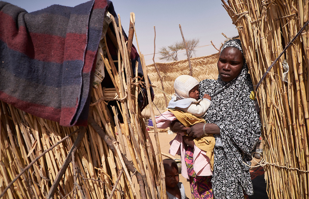 Falmata and her children in the village of Guidan Kaji near the border with Nigeria on the outskirts of Diffa, Niger on February 13, 2016. hey traveled to the village from Nigeria  and were displaced 5 times in the last year, crossing 2 countries. They received blankets and clothes from Caritas during the last distribution. Displaced people from Niger and Nigeria are sheltering in the village after fleeing at the nearby border. Many of the families had witnessed attacks by Boko Haram in their villages or had fled because of other villages around them being attacked. Caritas undertook a distribution of sleeping covers, mosquito nets, pots and money transfers.