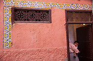 A woman holds a toddler while standing near the doorway of a public hammam in the medina of Marrakech, Morocco.