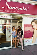 Two young women coming out of a self tanning salon, Brighton 2009