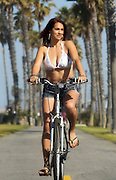 Woman Biking On The Boardwalk At The Beach