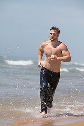 shirtless man in jeans running in the ocean