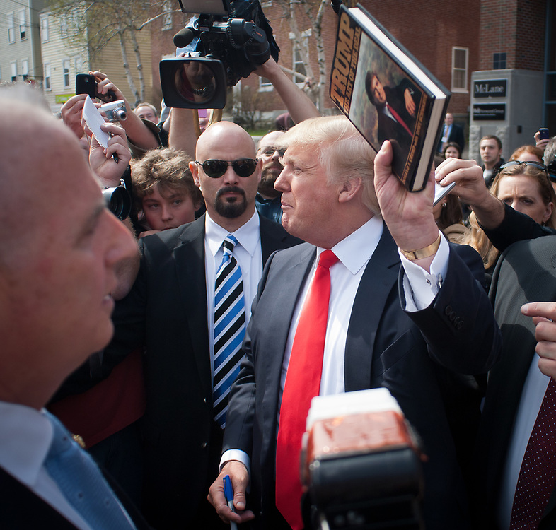 Donald Trump holds up a copy of his book after signing it for a Trump fan. Real Estate Mogul, TV Star and Presidential hopeful Donald Trump makes a visit to Portsmouth, NH for meetings and a meet and greet as he walks around Downtown Portsmouth.