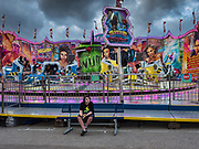 14 AUGUST 2019 - DES MOINES, IOWA: A teenager sits in front of the Magnum ride at the Iowa State Fair. The Iowa State Fair is one of the largest state fairs in the U.S. More than one million people usually visit the fair during its ten day run. The 2019 fair run from August 8 to 18.                PHOTO BY JACK KURTZ