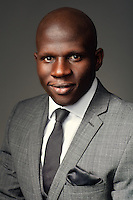 Corporate headshot dark grey background features black businessman in grey suit with hanky in pocket