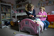 Babysitter Kelly Losure and Jenna Waugh play in Jenna's room while Jenna's mother Kelly Waugh is busy home schooling her two sons on Jan. 31, 2006. Kelly Waugh says Losure's care giving has been a big help. Before the family hired a babysitter, Waugh had to juggle Jenna while home schooling her sons every day of the week. .