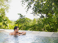 Mid adult man sitting in pool looking at view