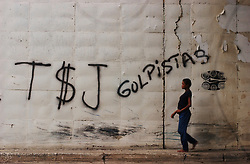 "A woman walks beneath an overpass by graffiti that reads ""The coup plotting Supreme Court"".  Today marks the end of the initial 10 day period the court had to designate members of the National Electoral Council.  The NEC is the body that will ultimately be able to authorize and validate signatures calling for a presidential recall."