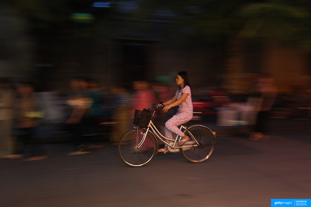 A street scene in Hoi An, Vietnam showing a women riding a bicycle in the early evening. Hoi An is an ancient town and an exceptionally well-preserved example of a South-East Asian trading port dating from the 15th century. Hoi An is now a major tourist attraction because of its history. Hoi An, Vietnam. 5th March 2012. Photo Tim Clayton