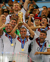 Captain Philipp Lahm of Germany lifts the FIFA World Cup trophy alongside his team mates after beating Argentina 1-0 and winning the FIFA World Cup Final