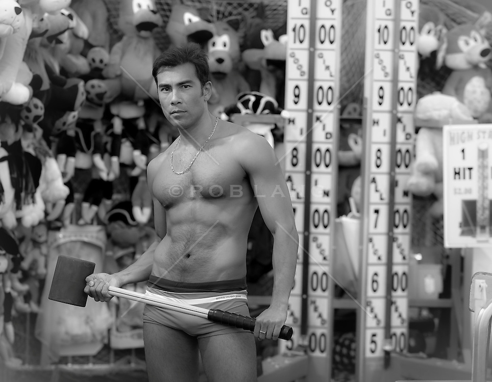 Shirtless Asian American man posing at a strength testing game in Coney Island, NY