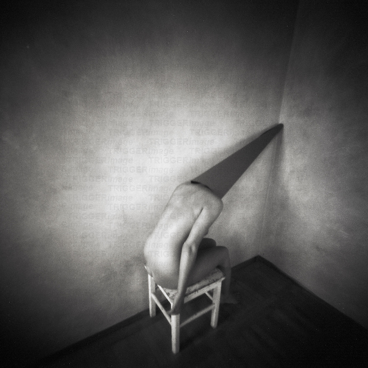 A naked woman wearing a pointed hat sitting on a stool in a room