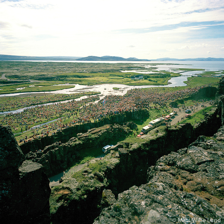 From the 1100 years celebration of the settlement of Iceland at Thingvellir 1974. View over Almannagja, Logberg to the farm and church at Thingvellir and the lake Thingvallavatn. South Iceland. Þingvellir á Landnámshátiðinn 1974. Séð yfir Almannagjá Lögberg og fram að Þingvallabær og Þingvallavatn. Þingvallahreppur.