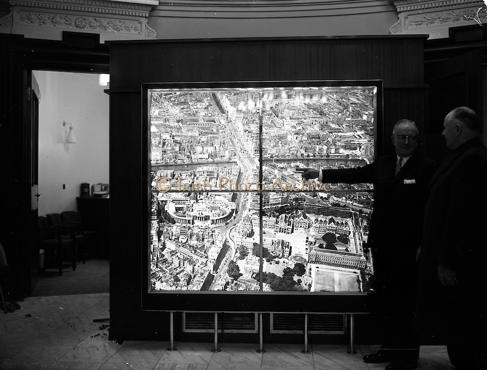 24/01/1962<br /> 01/24/1962<br /> 24 January 1962<br /> Illuminated map at Ulster Bank, College Green, Dublin. A large hand coloured illuminated photograph depicting the principal feature of central Dublin was put on display in Ulster Bank. It was an aerial view of the city centre enlarged to five feet by five feet nine inches from a transparency of 5 by 4 inches. The bank felt that it would be of interest to customers and tourists alike. Picture shows the manager of the bank, Mr S. le F. Killingley pointing out a landmark to a customer.