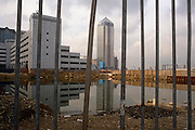 The still new Canary Wharf tower stands tall in the distance with a foreground of a city in turmoil. A still derelict space occupies the space where large offices will be built in the future. Fences stop trespassers from entering a water-filled hole on wasteland. This docklands development in east London is the product of the 1980s financial boom when during the office of Prime Minister Margaret Thatcher, huge building projects such as the Docklands consortium saw vast changes in London's landscape. The centrepiece was 1, Canada Square, also known as the Canary Wharf tower.