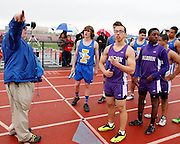 Teams from Irondequoit and Albion listen to instructions before the 4x100-meter relay at the His and Her track and field invitational at Penfield High School on Saturday, April 26, 2014.