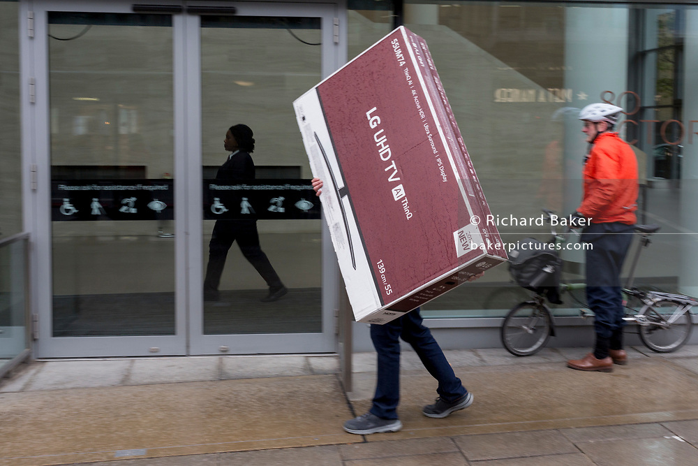 A slightly blurred man carries a box Ultra High-Definition TV along the street in Victoria, on 17th October 2019, in London, England.
