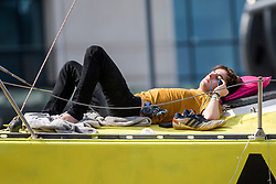 © Licensed to London News Pictures. 17/07/2019. Leeds, UK. An activist sun bathes on top of a boat this morning as the Extinction Rebellion protest enters its third day in Leeds where activist's have blocked Victoria Bridge in the city centre with a boat & tents. The protest is part of Extinction Rebellion's 'summer uprising' campaign, which has seen similar blockades in London, Cardiff, Bristol and Glasgow & is expected to last until Friday. Photo credit: Andrew McCaren/LNP