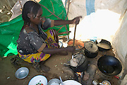 The Breidjing Refugee Camp, Eastern Chad on the Sudanese border shelters 30,000 people who have fled their homes in Darfur, Sudan. To feed her family, a woman stirs a pot of aiysh, the thick porridge that this refugee family eats three times a day. (Supporting image from the project Hungry Planet: What the World Eats.)