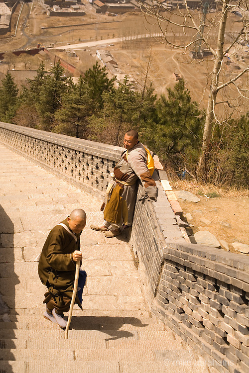 Two pilgrims climbing up the steps to a temple in Wutai Shan, People's Republic of China