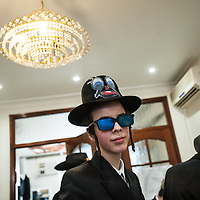 London, UK - 16 March 2014: a young men from the Orthodox Jewish community of Stamford Hill wearing sunglasses celebrates the festivity of Purim, dancing and singing in the streets at the sound of Yiddish music and visiting wealthy businessmen collecting for their charity