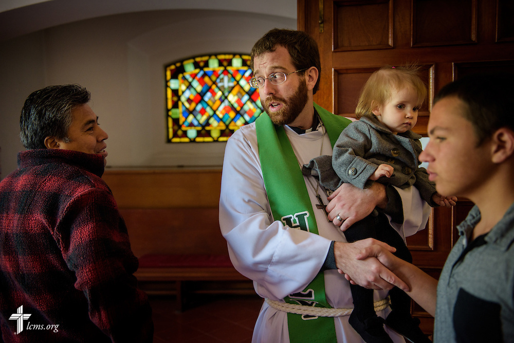 The Rev. Andrew Schlund, LCMS missionary to Mexico, holds his daughter Charlotte as he meets church members and visitors following worship at the Lutheran Church of The Good Shepherd on Sunday, Jan. 15, 2017, in Mexico City. LCMS Communications/Erik M. Lunsford