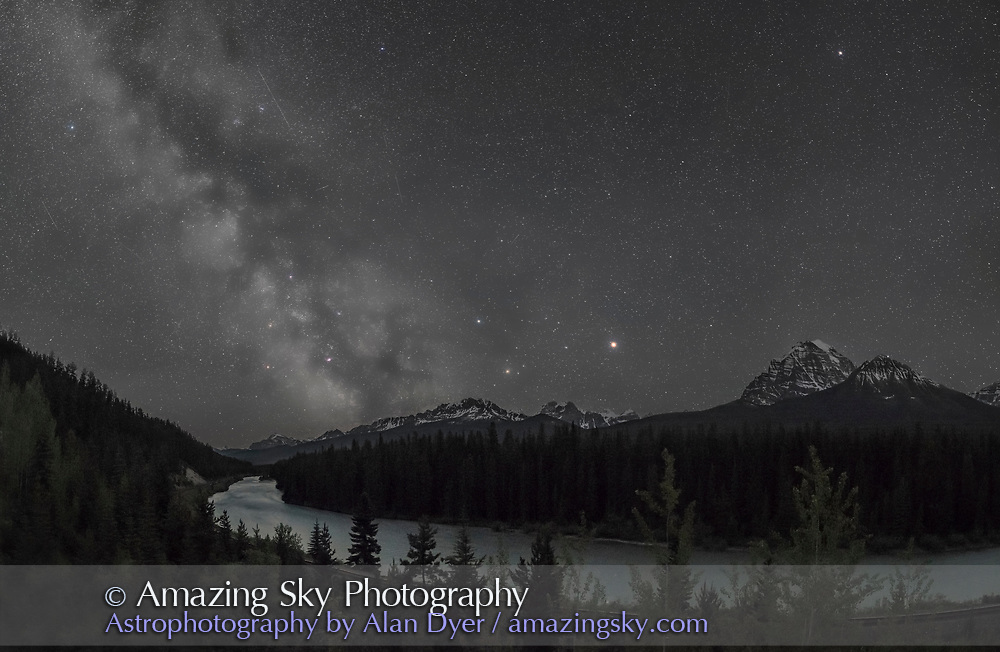 The Milky Way, often described in mythologies as a river in the sky, shines over the Bow River in Banff National Park on a very clear night in early June.<br /> <br /> The viewpoint is the famous Morant&rsquo;s Curve on the Bow Valley Parkway, overlooking the Bow, the CPR rail line following the river, and the peaks of the Continental Divide, including Mt. Temple at right near Lake Louise. The location is named for Nicolas Morant who photographed trains in the Rockies using large format cameras from here when under the employ of the CPR. <br /> <br /> Mars is the bright object at centre, west of Scorpius with Antares and Saturn, then to the east, the star clouds of the galactic centre region of the Milky Way above the southern horizon, in Sagittarius. The Milky Way extends up into Scutum, Serpens, and Aquila. The sky is not black but a deep blue from the perpetual twilight in the sky in early June (this was June 4, 2016) at this latitude. Some green airglow also discolours the sky. Several satellite trails are in the sky as well. <br /> <br /> This is a stitch of 9 panels to form a partial panorama, looking south and west, each exposure being 20 seconds at f/2.5 with the 24mm Sigma Art lens and Nikon D750 at ISO 5000. Shot with the iPano panning unit and stitched with PTGui. This version of the image has been processed to make the view better resemble what you see with the unaided eye, in a largely monochrome and softer view than the colourful and high-contrast views commonly presented in astrophotos. Even at that there is more fine structure present in the Milky Way than the unaided eye usually sees, though binoculars beging to reveal that smaller detail. I have left some colours in some stars and in the foreground of landscape scenes.