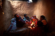 Sugia Devi, pregnant with her first child, has her feet massaged by her sister Muna Devi as midwives look on during a difficult labor that ended up lasting two full nights and involved three midwives and the village doctor, in the mud home where she lives with her husband's family in Mounia village, Bihar, India.
