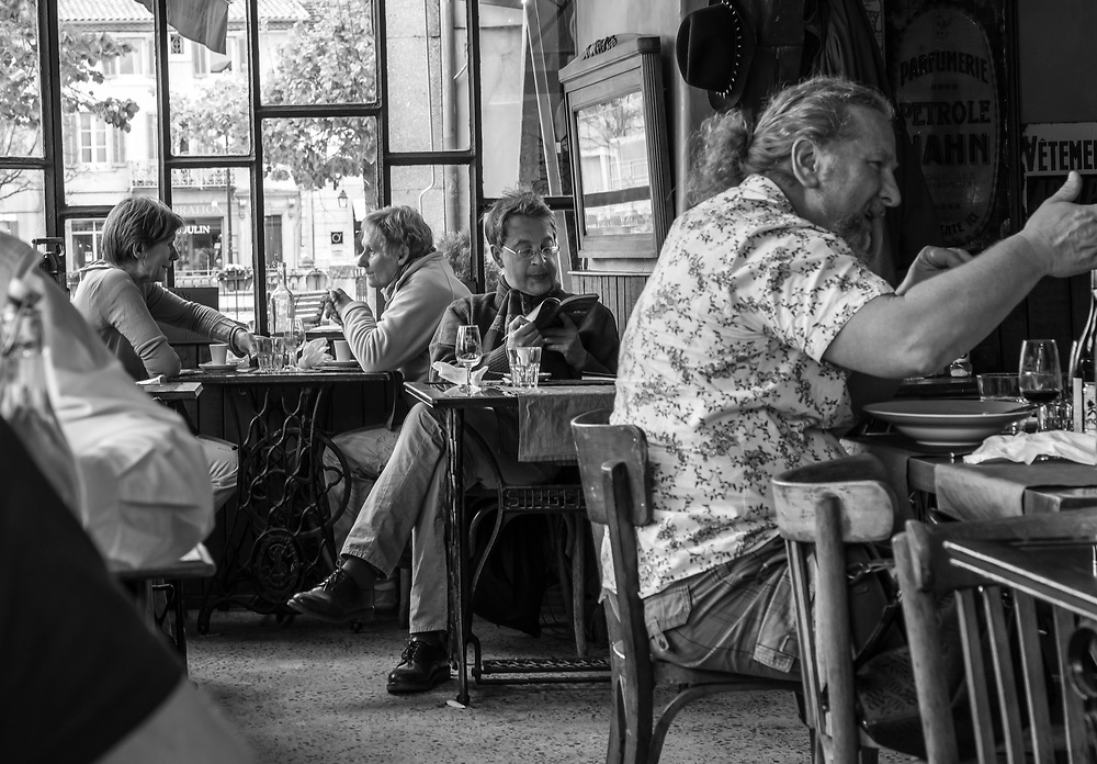One setting - three stories. The man in the foreground conveys his excitement with his hand gestures. Oblivious to the rest of the world, the man in the middle, maybe a tourist, enjoys leisurely reading his book and sipping his drink. The women in the background are engaged in a very personal talk reflected by the intimate atmosphere of the cafe. L'Isle-sur-la-Sorgue , France.