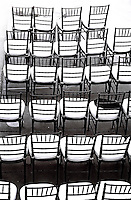 veritcal photograph of chiavari chairs placed in a row with white cushions black and white film