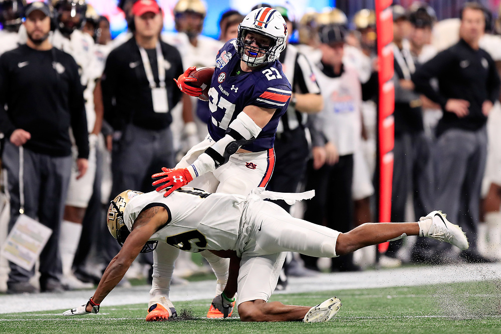 Auburn Tigers fullback Chandler Cox (27) is tackled by UCF Knights defensive back Mike Hughes (19) during the 2018 Chick-fil-A Peach Bowl NCAA football game on Monday, January 1, 2018 in Atlanta. (Paul Abell / Abell Images for the Chick-fil-A Peach Bowl)